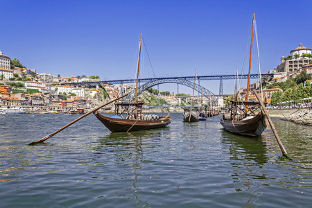 The iconic Rabelo Boats, the traditional Port Wine transports, with the Ribeira District and the Dom Luis I Bridge over the Douro River  Porto, Portugal   photo