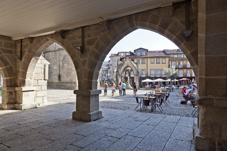 townhall: Guimaraes, Portugal - October 13, 2013  People enjoying the esplanades in the Oliveira Square, seen through the old Town-Hall arcade  UNESCO World Heritage Site