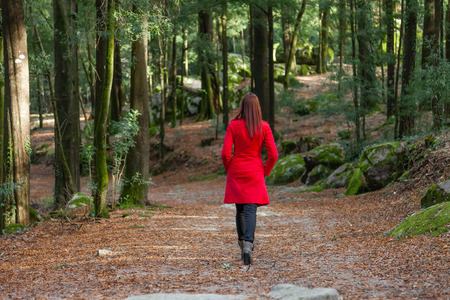 Young woman walking away alone on a forest path wearing a red overcoat