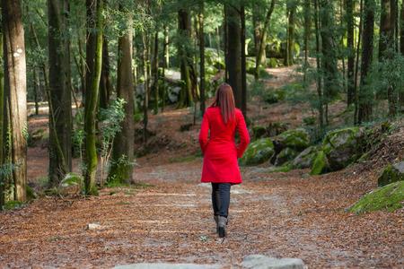kurtka: Młoda kobieta idzie się samotnie na leśnej drodze ubrana w czerwony płaszcz