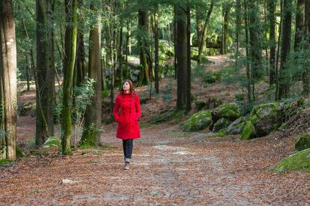 elegant woman: Mujer joven caminando sola en una pista forestal que lleva un abrigo rojo