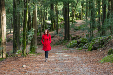 Young woman walking alone on a forest path wearing a red overcoat