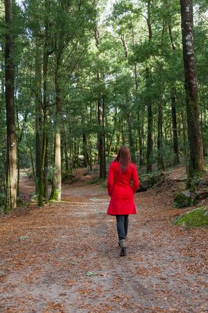Jonge vrouw lopen weg alleen op een bospad draagt een rode jas