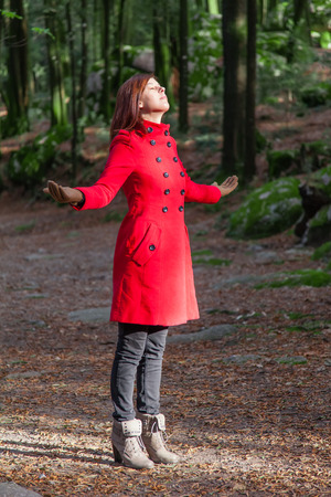Woman enjoying the warmth of the winter sunlight on a forest wearing a red overcoat Stock Photo