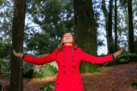 warmness: Woman enjoying the warmth of the winter sunlight on a forest wearing a red overcoat Stock Photo