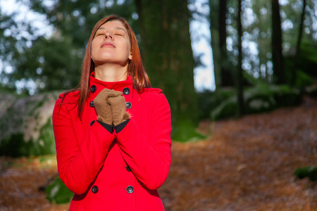 grateful: Woman enjoying the warmth of the winter sunlight on a forest wearing a red overcoat Stock Photo