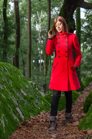 Young woman feeling sad walking on a forest wearing a red overcoat during winter under a sunlight ray photo