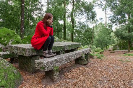 Sentimiento Mujer joven deprimida que se sienta en una mesa de piedra y Banco en un bosque que llevaba un abrigo rojo durante el invierno Foto de archivo - 35820877
