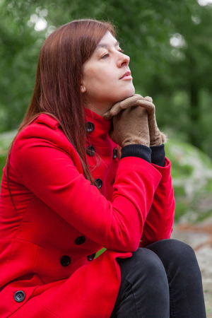 shrunken: Young woman feeling depressed sitting on a stone table and bench on a forest wearing a red overcoat during winter