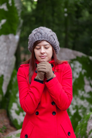 shivering: Young woman shivering with cold on a forest wearing a red overcoat, a beanie and gloves during winter