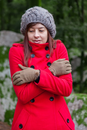 shrunken: Young woman shivering with cold and embracing herself on a forest wearing a red overcoat, a beanie and gloves during winter