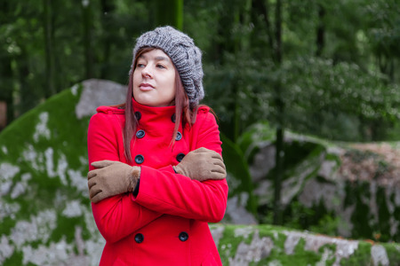 shivering: Young woman shivering with cold and embracing herself on a forest wearing a red overcoat, a beanie and gloves during winter