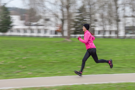 Young woman running on a cold winter day in an urban park with a panning effect. photo