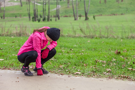 to crouch: Young woman exhausted after running on a cold winter day in the track of an urban park.
