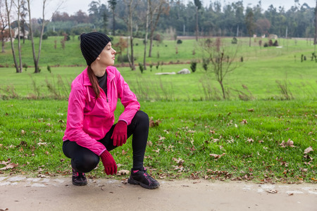 to crouch: Young woman analyzing the track before running on a cold winter day in an urban park.
