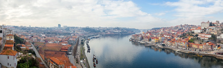 rabelo: Panorama of the historical Ribeira District and Douro River in the city of Porto, as well the Vila Nova de Gaia Port Wine Cellars and Rabelo Boats in Portugal during sunset.