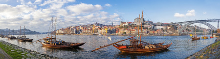 ribeira: The iconic Rabelo Boats, the traditional Port Wine transports, with the Ribeira District and the Dom Luis I Bridge over the Douro River. Porto, Portugal.  Stock Photo
