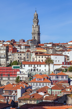 standing out: The iconic Clerigos Tower in the city of Porto, Portugal. One of the landmarks and symbols of the city, standing out from the city rooftops.
