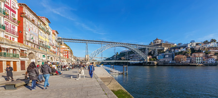 dom: Porto, Portugal. December 29, 2014: Tourists and locals enjoy the Ribeira District scenery and the sun in the Douro River bank near the Dom Luis I Bridge. Unesco World Heritage.