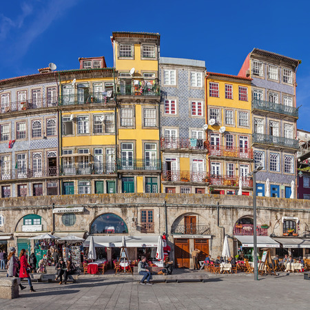 historic site: Porto, Portugal. December 29, 2014: The typical colorful buildings of the Ribeira District with the popular shops, restaurants and bars built in the stone wall. Unesco World Heritage Site. Editorial