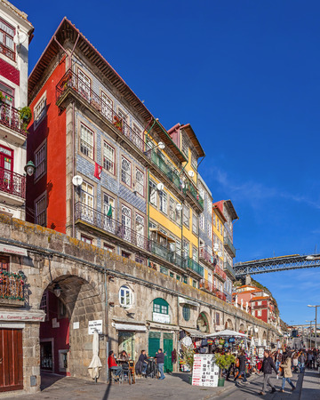 Porto, Portugal. December 29, 2014: The typical colorful buildings of the Ribeira District with the popular shops, restaurants and bars built in the stone wall. Unesco World Heritage Site.