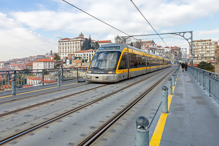 rio: Porto, Portugal. January 5, 2015: Porto Subway train passes by the superior deck of the Dom Luis I bridge connecting Gaia to the city of Porto, seen in the background, over the Douro River. Portugal