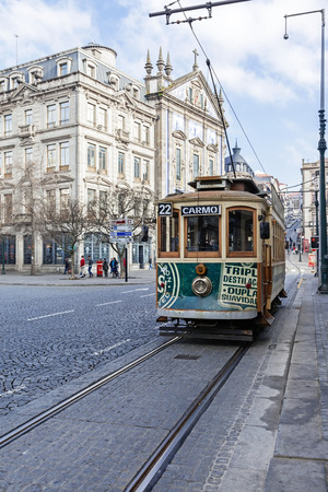 garret: Porto, Portugal. January 5, 2015: The old tram passes by the Aliados Avenue and Liberdade Square towards the Almeida Garret Square with the Congregados Church on the left. Unesco World Heritage Site