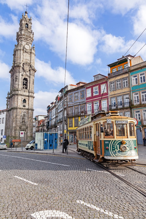 electrico: Porto, Portugal. January 5, 2015: The old tram passes by the Clerigos Tower, one of the landmarks and symbols of the city. Unesco World Heritage Site