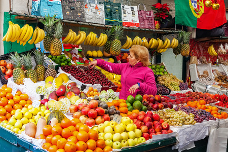 Porto, Portugal. December 29, 2014: Fruit seller organizing and taking care of the stand in the interior of the historical Bolhao Market Editorial