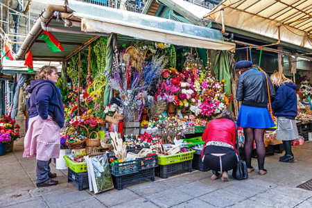 costumers: Porto, Portugal. December 29, 2014: Artificial flowers stand in the interior of the historical Bolhao Market