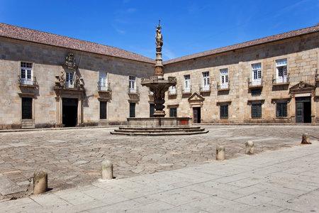 european culture: Braga, Portugal - July 27, 2015: Baroque Castelos Fountain in Paco Square, and the baroque facade of the Nursing School of the Minho University