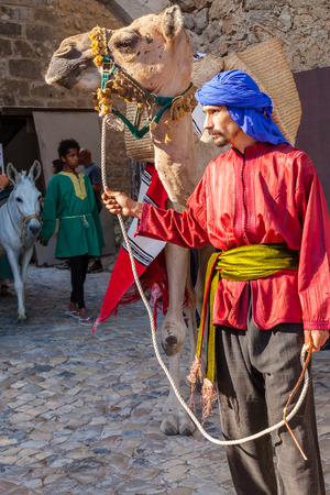 reenactment re enactment: Obidos, Portugal - August 09, 2015: Moorish man with dromedary camel in the parade of the Medieval Market reenactment. The Medieval Market festival is very popular among tourists. Editorial