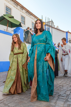 re enactment: Obidos, Portugal - August 09, 2015: Noble ladies in the parade of the Medieval Market reenactment. The Medieval Market festival is very popular among tourists.