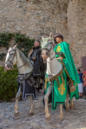 re enactment: Obidos, Portugal - August 09, 2015: Knights riding white horses in the parade of the Medieval Market reenactment. The Medieval Market festival is very popular among tourists. Editorial