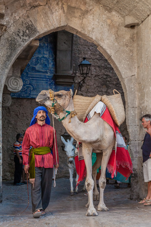 reenactment re enactment: Obidos; Portugal - August 09; 2015: Moorish man with dromedary camel in the parade of the Medieval Market reenactment. The Medieval Market festival is very popular among tourists. Editorial