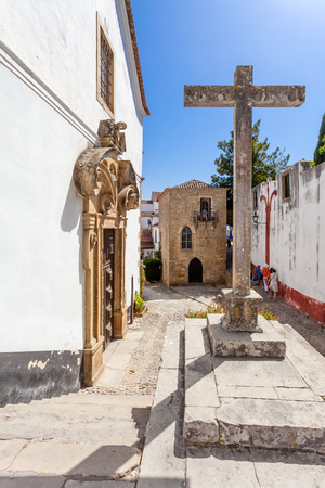 sephardi: Obidos, Portugal - August, 2015: Misericordia Church with the Medieval Sephardic Synagogue in background. Obidos is a medieval town inside walls, and very popular among tourists.
