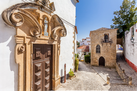 sephardi: Obidos, Portugal - August, 2015: Misericordia Church portal and the Medieval Sephardic Synagogue in background. Obidos is a medieval town inside walls, and very popular among tourists. Editorial