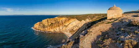 senhora: One of the promontories and bays of the Espichel Cape, with the remote Hermitage of the Sanctuary of Nossa Senhora da Pedra Mua, built on the edge of a cliff during sunset. Sesimbra, Portugal.
