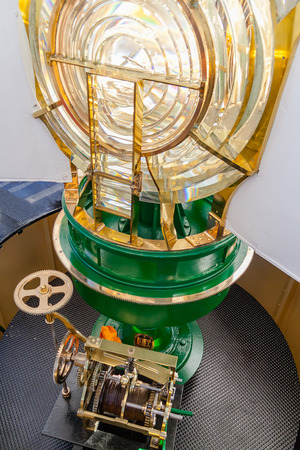 fails: Lit Lighthouse light, with a view of the Fresnel optic system and the old clock mechanism at the bottom, still in use if the modern engine fails. Espichel Cape Lighthouse in Sesimbra, Portugal. Stock Photo