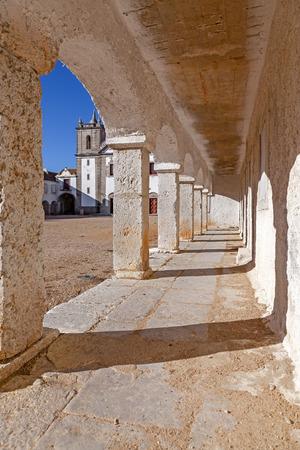 lodgings: The arcades of the pilgrim lodgings in the Baroque Sanctuary of Nossa Senhora do Cabo, aka Nossa Senhora da Pedra Mua in Espichel Cape and the church at the back. Sesimbra, Portugal Stock Photo