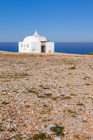 senhora: The remote Ermida da Memoria Memory Hermitage of the Nossa Senhora do Cabo Sanctuary, built on the edge of a cliff on Espichel Cape, with the Atlantic Ocean in background. Sesimbra, Portugal. Stock Photo