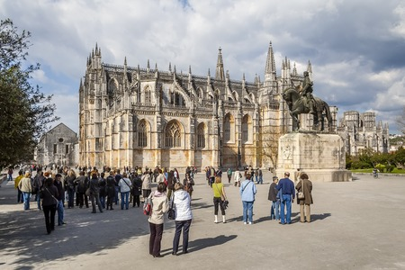 Batalha, Portugal - April 05, 2015: Tourists gathering around for a guided tour of the monastery. UNESCO World Heritage Site.