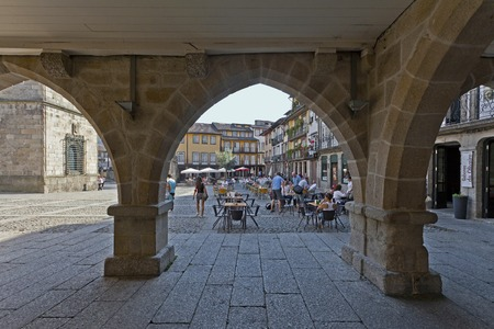 townhall: Guimaraes, Portugal - October, 2015: People enjoying the esplanades in the Oliveira Square, seen through the old Town-Hall arcade. UNESCO World Heritage Site. Editorial
