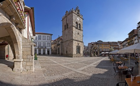 senhora: Guimaraes, Portugal - October, 2015: People enjoying the esplanades in the Oliveira Square with the Nossa Senhora da Oliveira Church, Salado Monument and old Town-Hall. Editorial