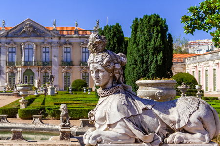 palacio: Queluz, Portugal. Sphinx sculpture at the Neptune gardens and Cerimonial Facade on the Queluz Royal Palace. Formerly used as the Summer residence by the Portuguese royal family.