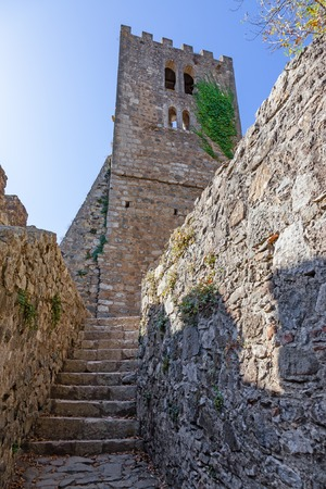 pena: Bell Tower ruins of the medieval Nossa Senhora da Pena Church aka Santa Maria da Pena in the Castle of Leiria, seen from a narrow passage. Leiria, Portugal.