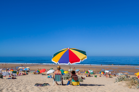 preferred: Almada, Portugal - July, 2015: Senior couple enjoying a day at the Fonte da Telha Beach in the Costa da Caparica coast, the preferred coast for Lisboans to beach.