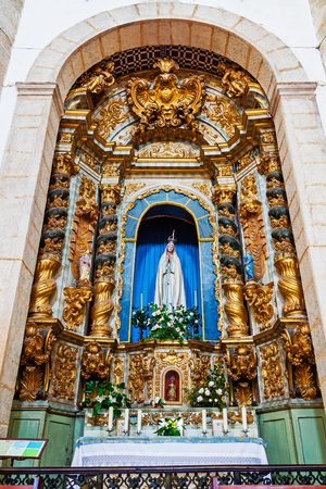 made in portugal: Evora, Portugal - December, 2015: A very rich baroque altar made of Gilded Woodcarving dedicated to Our Lady of Fatima. Santo Anto Church
