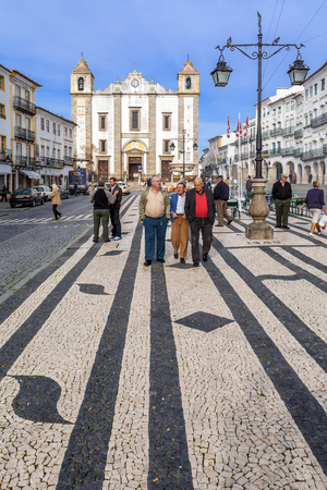 locals: Evora, Portugal - December, 2015: Locals strolling in the Giraldo Square with the typical Portuguese cobblestone pavement and the Santo Antao Church in background. UNESCO World Heritage Site.