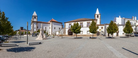 v shape: Dom Pedro V Square in Castelo de Vide. Santa Maria da Devesa church (left) and City-Hall (center). Alto Alentejo, Portugal Stock Photo